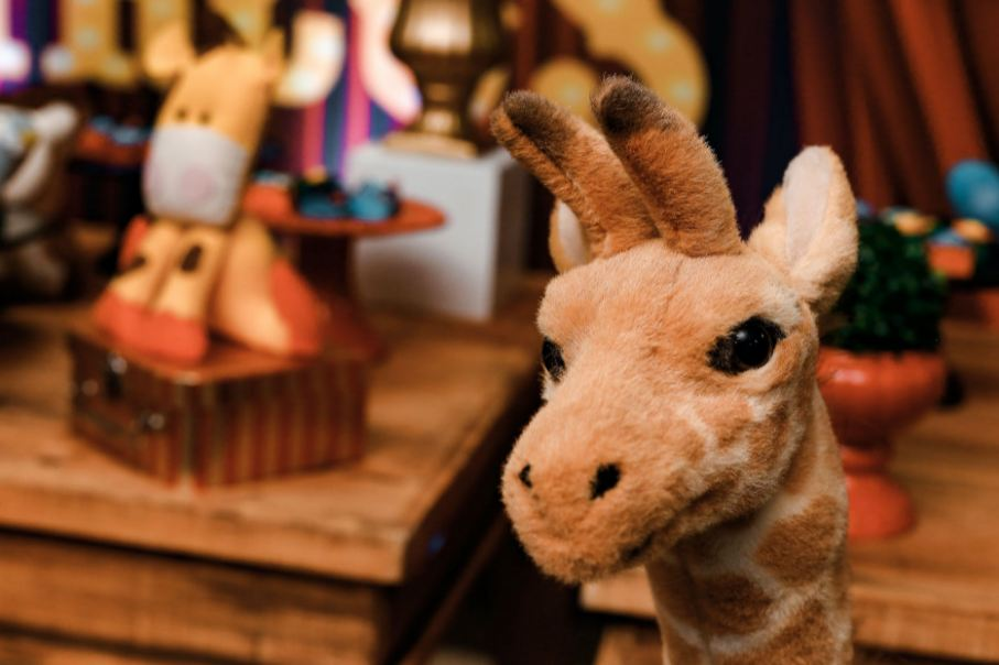Giraffe plush toy with other toys in the background.